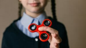 autistic girl stimming fidget spinner