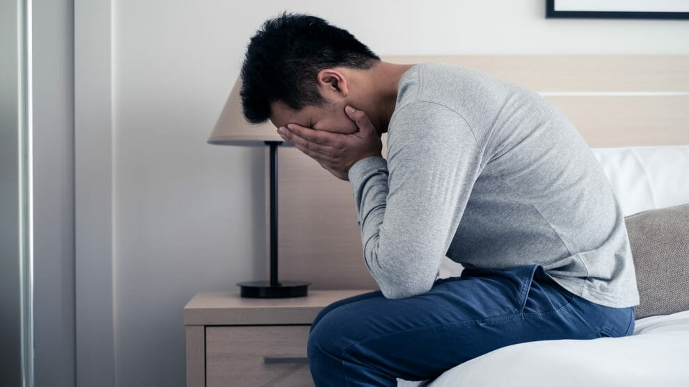 Depressed father sitting on bed