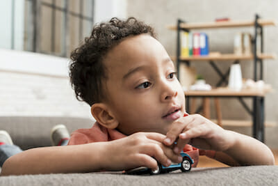 autistic boy playing with car