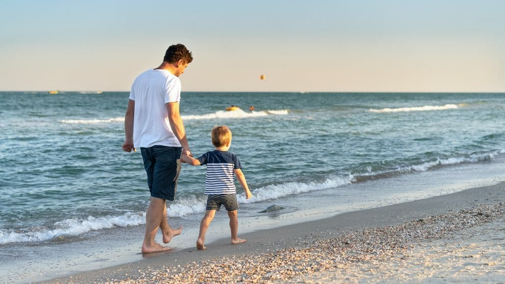 Father and autistic son walking on beach